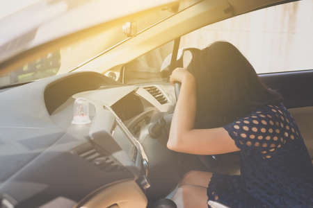 Asian woman sleepy tired and have a headache while driving car