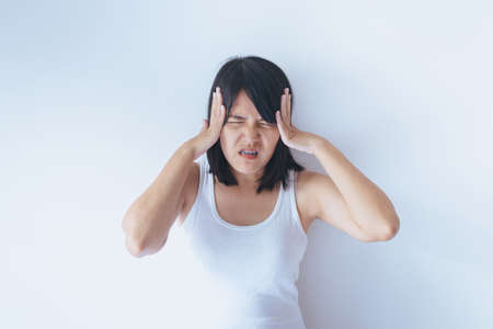 Asian woman on a white background hand holding her sick ear,Tinnitus