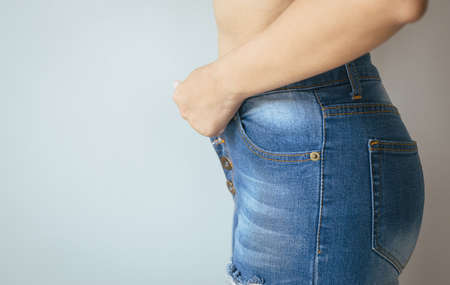 Woman attempt putting or wearing her pants in dressing room