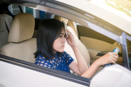 Asian woman having hot beacuse a heat wave in her car,Broken air conditioner