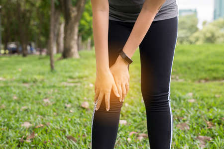 Woman suffering from pain in leg and knee injury after sport exercise running jogging and workout outdoor Banque d'images