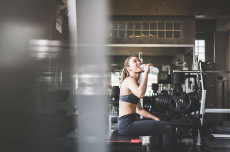 Attractive fitness woman sitting and drinking water in gym,Asian female break and relex after workout
