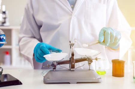 Chemist hand using scales weighing with medicine in lab