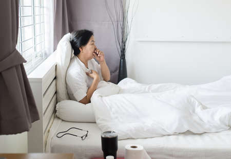 Elderly asian woman coughing and sitting on her bed,Concept of health