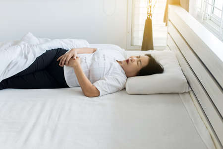 Elderly asian woman having painful stomachache on bedroom,Female suffering from abdominal pain while lying in bedroom