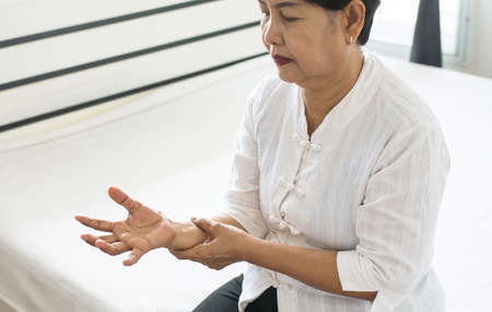 Elderly woman looking her hand and suffering with parkinsons disease symptoms 스톡 콘텐츠