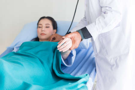 Man doctor holding hand and using stethoscope to asian woman patient and follow up treatment at hospital