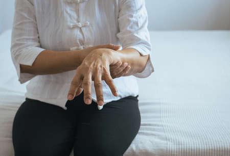 Donna anziana che soffre di sintomi del morbo di Parkinson a portata di mano