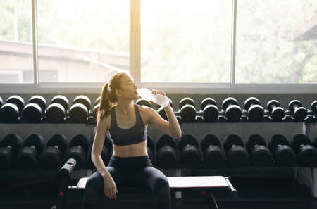 Attractive sporty woman sitting and drinking water in gym,Asian young female break and relex after workout