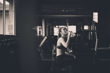 Attractive woman sitting and drinking water in gym,Asian female break and relex after workout,Black and white toned