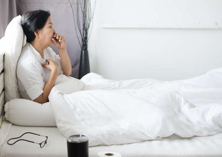 Elderly people asian woman coughing and sitting on her bed,Female sore throat,Concept of health