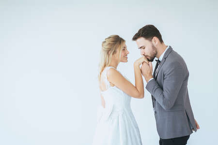 Portrait of groom with bride kissing in her hand on white background,Happy and smiling in engagement day,Copy space and white background