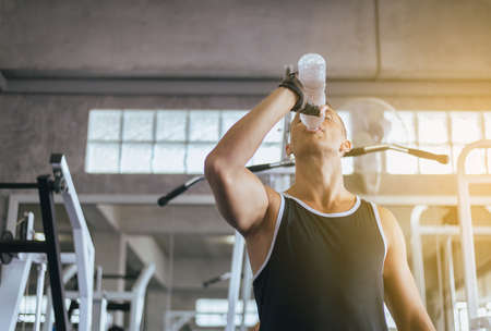 Attractive man drinking water in gym,Men break and relex after workout