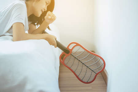 Beautiful asian woman using mosquito swatter at house,Female with mosquito electric net racket in bedroom Zdjęcie Seryjne
