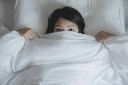 Woman with scare and panic while lying down under the blanket in bedroom,Nightmare or bad dream Archivio Fotografico