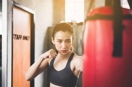 Woman boxer punching at a boxing gym,Women boxer training on punching bag