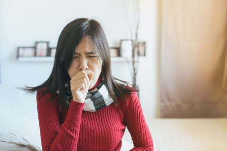 Asian woman coughing with sore throat,Female suffering with cough a lot in bedroom