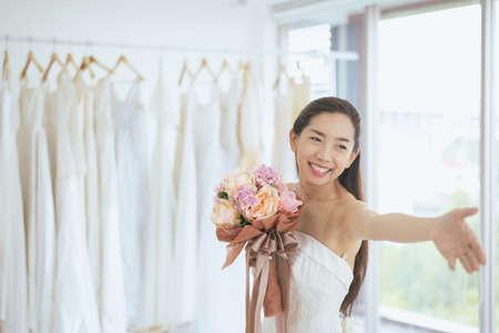 Sposa felice donna asiatica sorridente o allegra mano che tiene fiori colorati