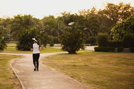 Young beautiful asian woman running in public park in the morning Archivio Fotografico