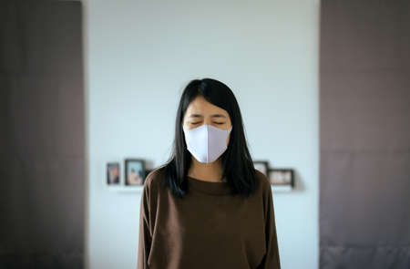 Asian woman using mask protect PM 2.5 because pollution in home,Young female got nose allergy