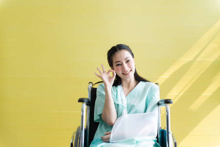 Asian beautiful woman patients raise up your hand OK sign symbol and sitting on wheelchair at hospital,Happy and smiling 版權商用圖片