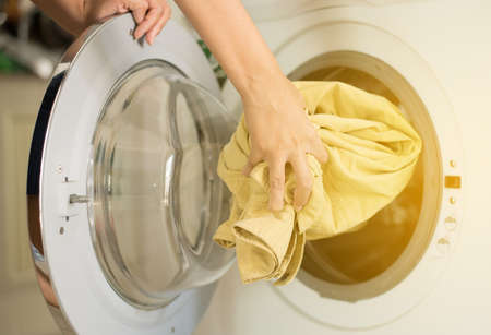 Hands female getting in dirty clothes into washing machine doing laundry at house