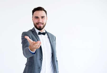 Homme en costume formel debout et montre la paume ouverte de la main tendue sur fond blanc avec espace de copie pour le texte, heureux et souriant Banque d'images