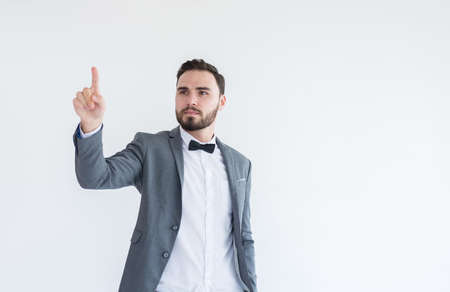 Man in formal suit standing hand touching virtual screen on white background with copy space for text