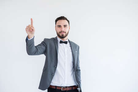 Man in formal suit with hands pointing and touching virtual screen on white background,Copy space for text