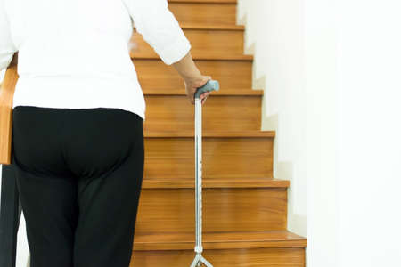 Elderly asian woman holding stick while walking up stair at home,Close up Reklamní fotografie - 120248071