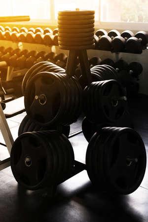 Cerca de barra y mancuernas en el gimnasio, equipo de entrenamiento con pesas en rack