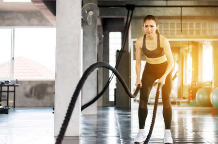 Sporty and slim asian woman using battle rope at gym,Female doing exercise in functional training