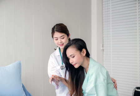 Asian doctor support to her patient female in hospital,Healthcare concept,Happy and smiling