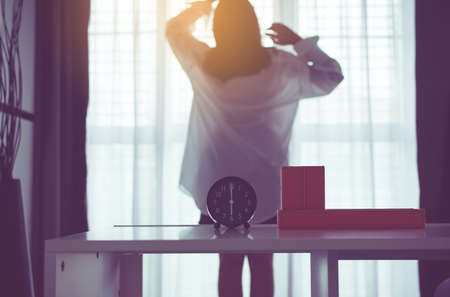 Blured of women stretch oneself and lazy in bedroom after waking up in the morning