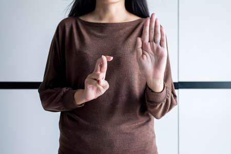 Mentire una donna con le dita incrociate a mano dicendo bugiardo e barare, concetto di pesce d'aprile, segnale di stop