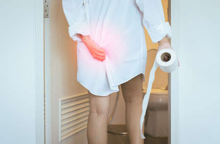 Women using toilet and suffers from Diarrhea and Hemorrhoids after wake up in morning at house Stock Photo
