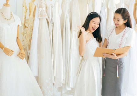 Portrait of happy asian woman holding credit card in wedding dress store owner,Beautiful female successful dressmaker in shop and small business Stock fotó