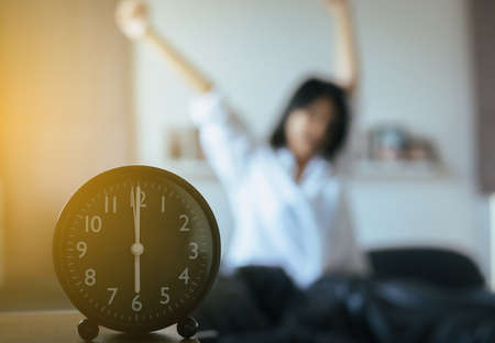 Blured of refreshing female in white shirt stretch lazy in bedroom after waking up at 6 o'clock in the morning,Alarm clock