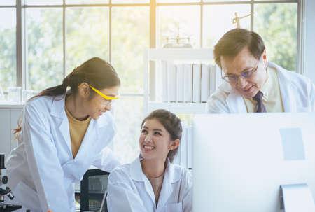 Grupo de estudiantes de medicina asiáticos que trabajan y analizan información de investigación de datos juntos en el laboratorio.