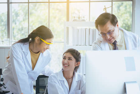 Gruppo di studenti di medicina asiatici che lavorano e analizzano insieme le informazioni sulla ricerca dei dati nel laboratorio