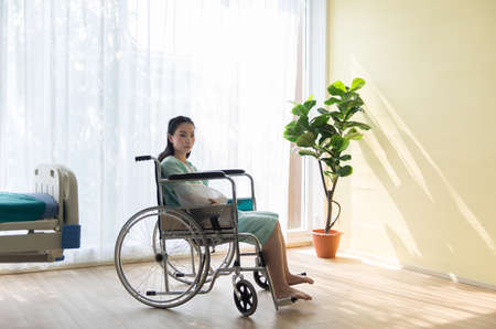 Lonely asian women patients broken arm while sitting in the wheelchair at hospital Banco de Imagens