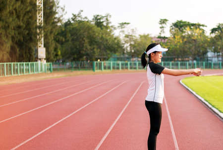 Asian beautiful woman static stretching and warming up before running or working out at public park Stockfoto