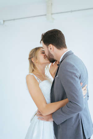 Loving and romantic couple is kissing with dance together on white background,Enjoying in wedding day Banco de Imagens