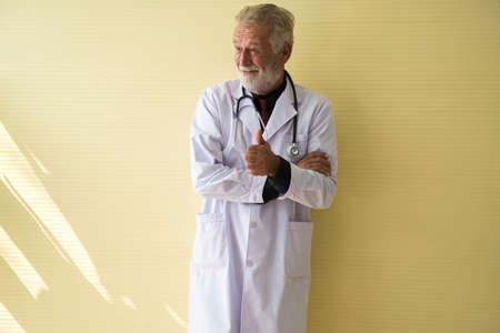 Portrait of senior doctor standing and showing thumb up at hospital,Happy and smiling positive thinking attitude,Copy space for text