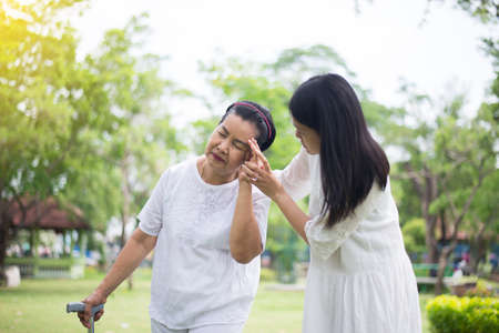 Elderly asian women having a headache suffering from migraine disease,Female take care and support