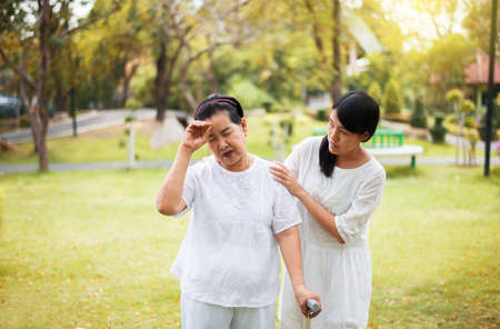 Elderly asian woman having a headache suffering from migraine disease,Daughter take care and support