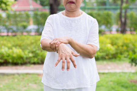 Elderly asian woman suffering with parkinson's disease symptoms