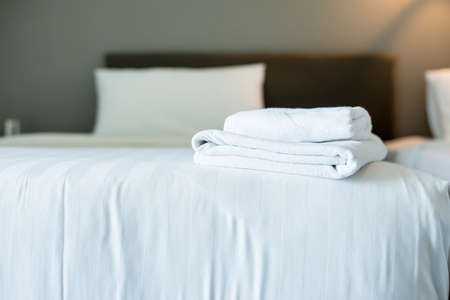White hotel towel on bed,Stack of fluffy bath towels,Close up,Copy space for text