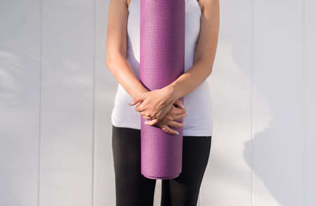 Women hands holding yoga mat purple color after a workout in the morning,Exercise equipment,Healthy fitness and sport concept,Copy space for text Reklamní fotografie