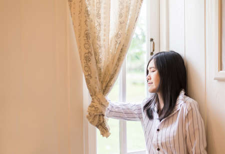 Portrait of beautiful asian female relax and standing near window at home,Positive thinking,Good attitude,Close your eyes